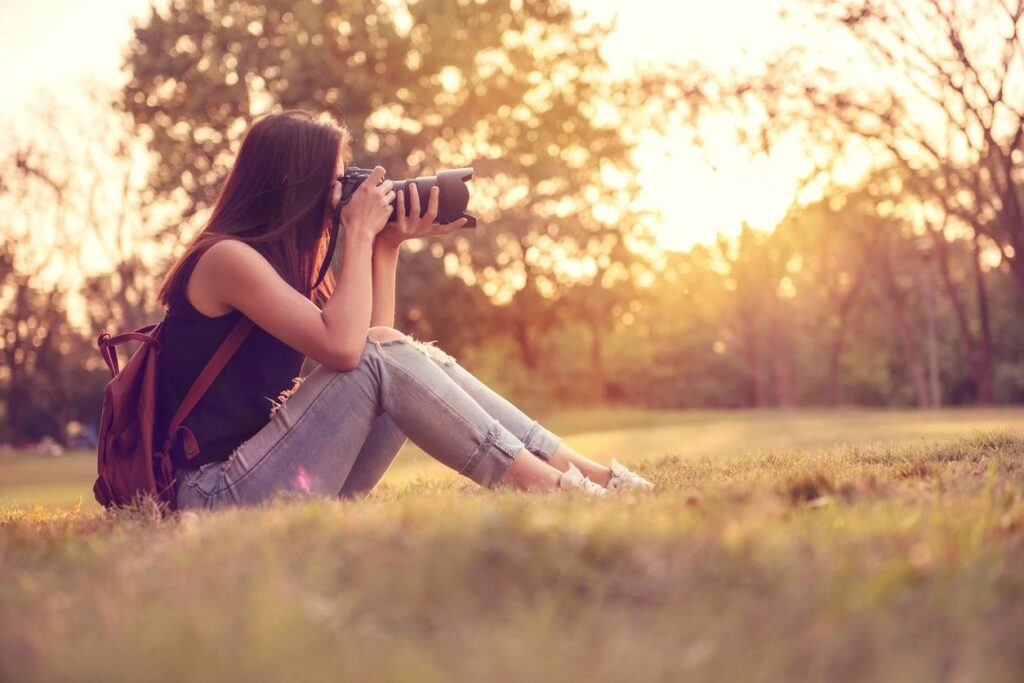 Woman sitting in a grassy field taking a picture with a DSLR camera.
