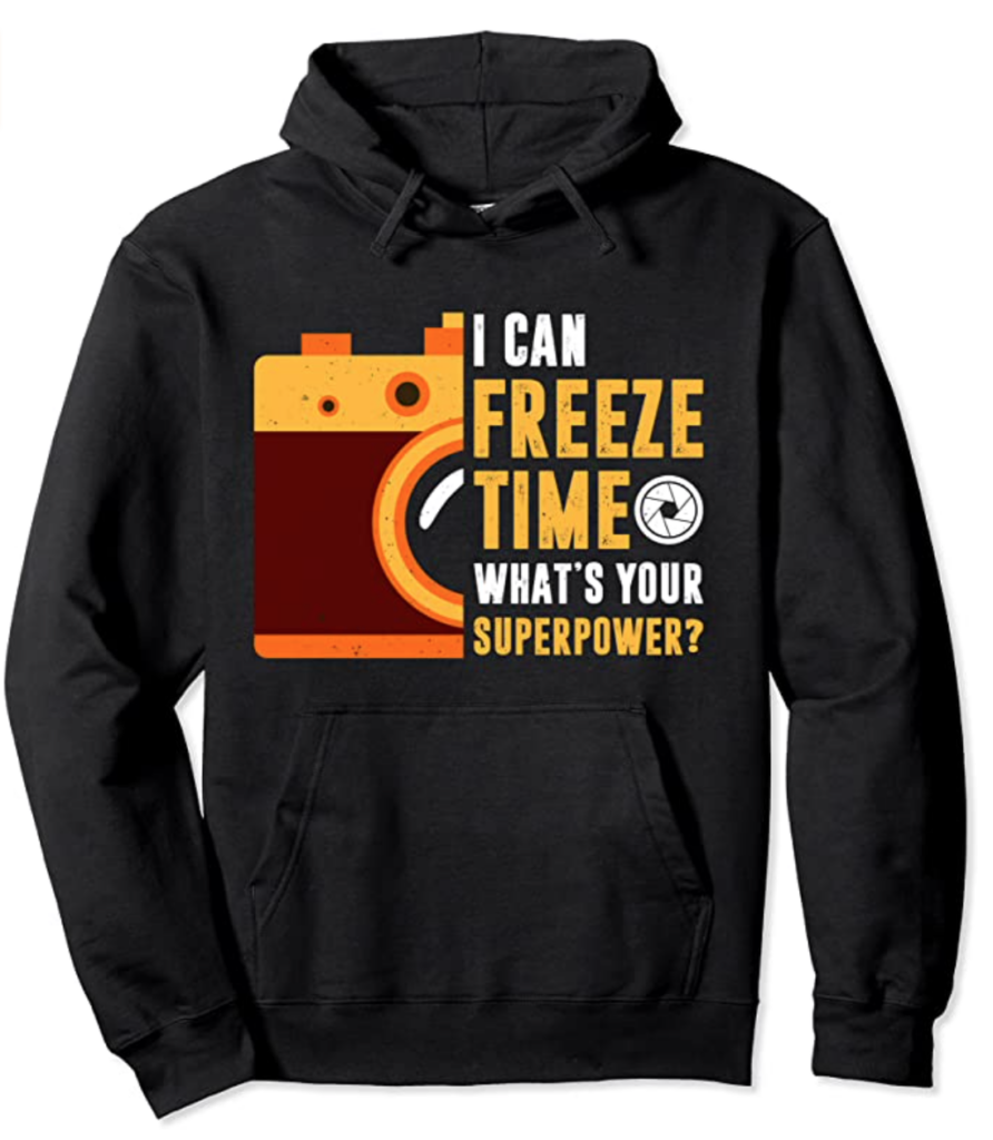 "Image of a hoodie with an image of a camera printed on it, as well as the phrase, ""I can freeze time, what's your super power?"""