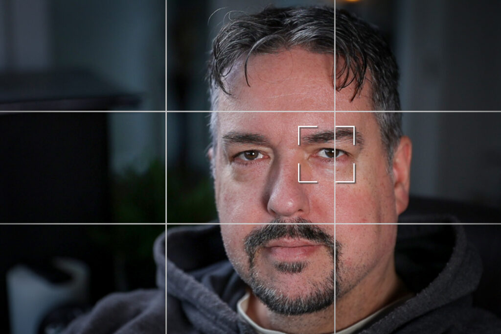 "Image of a man seen though ""live view"" with grid lines, and eye-detect autofocus box over the nearest eye."
